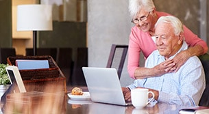 Elderly couple seated at a table reading about COPD on a laptop