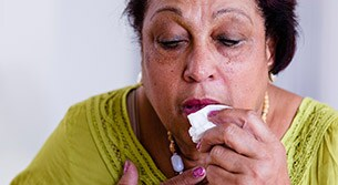 Lady experiencing COPD flare-up holding handkerchief to her face