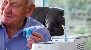 Gentleman about to start his nebuliser COPD therapy using a Philips InnoSpire Deluxe.