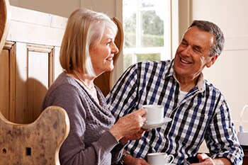 Laughing couple seated managing his COPD in daily life