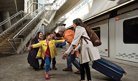Family being greeted at train station, women using SimplyGo Mini